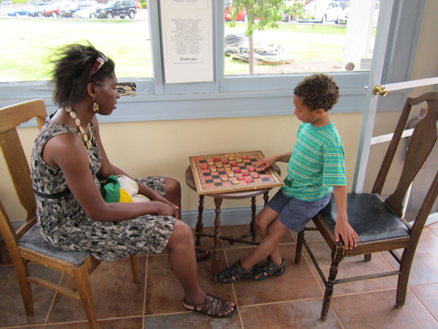 Joanitha and Joachim playing checkers, DePere, Wisconsin, 2011