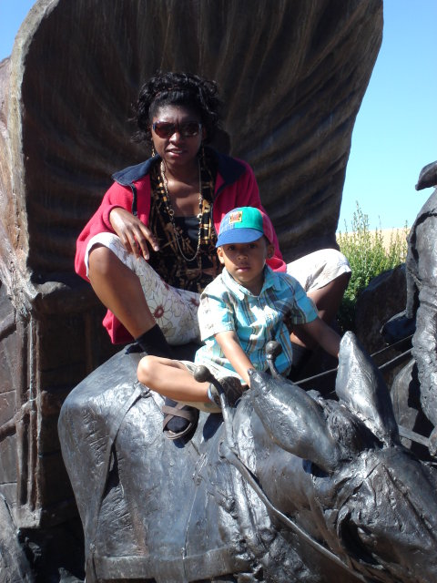 Joanitha and Joachim on a bronze covered wagon, Santa Fe, New Mexico, 2009