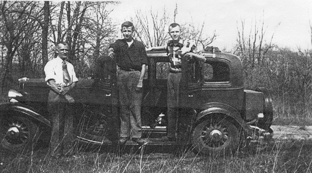 Michael Vogl and two sons by an old car, , Wisconsin, 1945